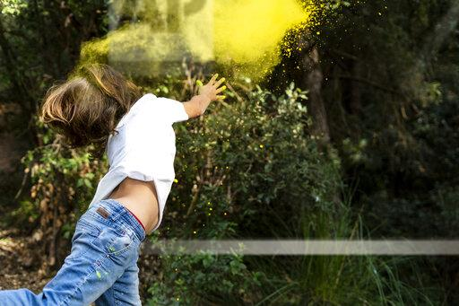 Boy throwing colorful powder paint, celebrating Holi, Festival of Colors