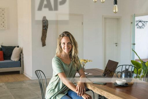 Portrait of smiling woman with laptop sitting at dining table at home