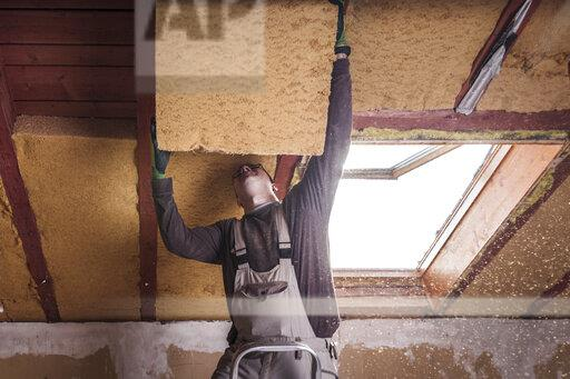 Roof insulation, worker filling pitched roof with wood fibre insulation
