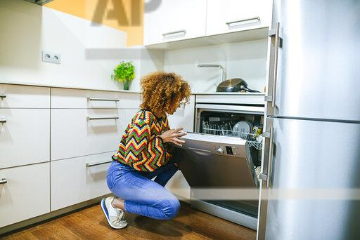Young woman with curly opening the dishwasher in kitchen