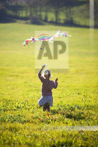 Little girl running in field with kite