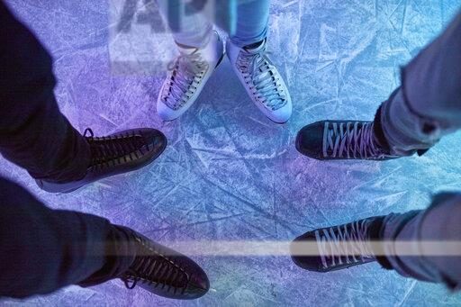 Legs of friends wearing ice skates standing on an ice rink