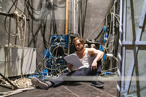Actor with script rehearsing backstage