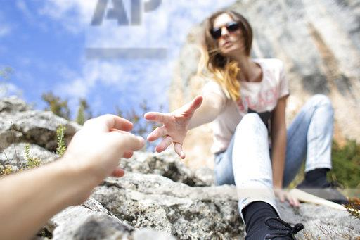 Spain, Alquezar, young woman on a hiking trip giving a helping hand