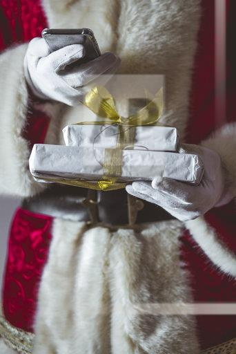 Santa Claus with smartphone and Christmas presents, partial view