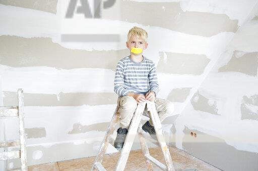 Angry boy with taped mouth sitting on ladder in attic to be renovated