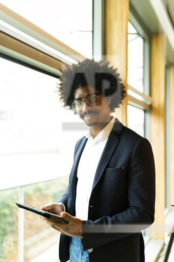 Portrait of confident businessman standing at the window using tablet