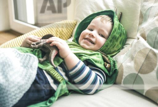 Happy boy in a costume lying down playing with toy figure at home