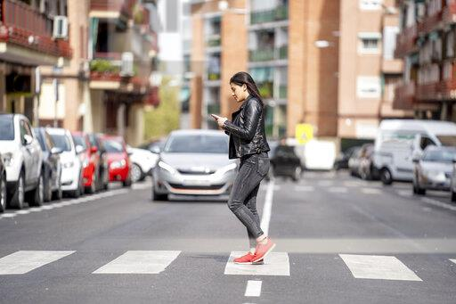 Young woman crossing the pedestrian crossing and using mobile phone