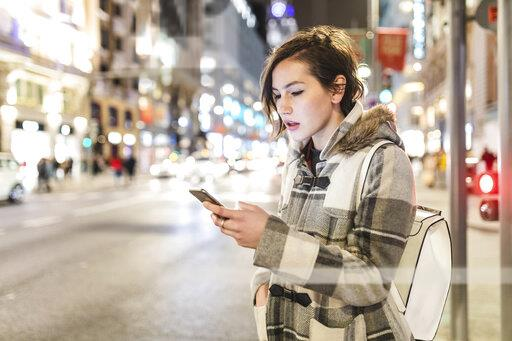 Spain, Madrid, young woman in the city at night using her smartphone
