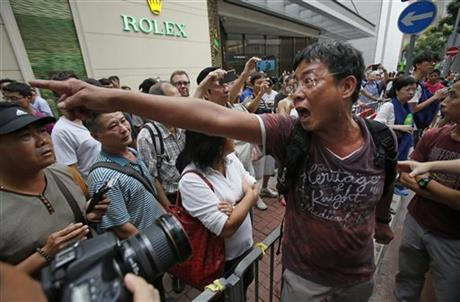 An angry local demands that the pro-democracy student protesters remove the barricades blocking streets in Causeway Bay, Hong Kong, Friday, Oct. 3, 2014. Crowds of pro-democracy protesters on the streets of Hong Kong dwindled sharply Friday after the territory's leader agreed to meet with their leaders over demands for electoral reforms. An afternoon thunderstorm — and sheer exhaustion after the weeklong protests — also appeared to keep people off the streets.