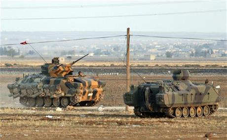 Turkish forces on armoured vehicles at the outskirts of Suruc, secure the border area with Syria, background, Monday, Oct. 6, 2014.