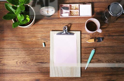 Clip board with blank pink paper, coffee mug and other utensils on desk at home office, top view