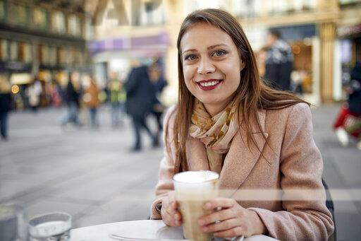 Austria, Vienna, portrait of smiling young woman drinking coffee at pavement cafe