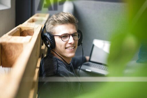 Smiling young man listening to music with headphones