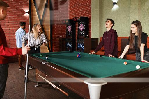 Happy friends playing billiards together