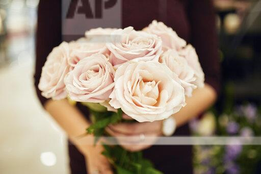 Close-up of woman holding bunch of roses