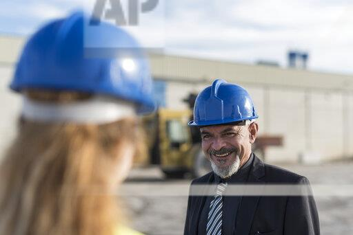 Portrait of businessman smiling at female worker on industrial site