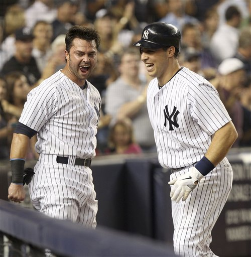 Mark Teixeira, right, is greeted by Nick Swisher