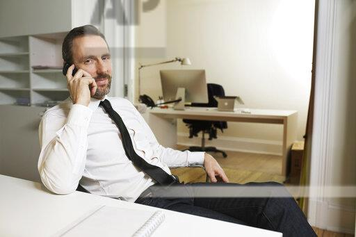 Businessman talking on the phone at desk in office