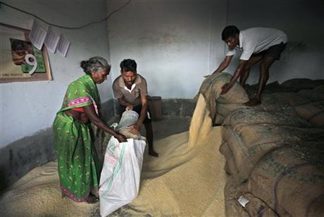 A tribal woman Rangamma, left, fills subsidised rice at a fair price shop under the Public Distribution System in...