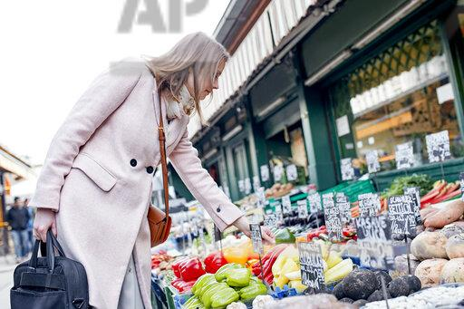 Austria, Vienna, young woman choosing vegetables at Naschmarkt