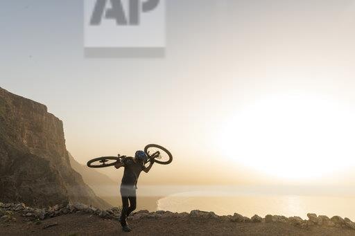 Spain, Lanzarote, mountainbiker on a trip at the coast at sunset carrying his bike
