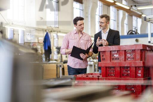 Two men in factory examining workpiece