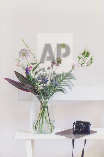 Flower vase and open calendar on white bench, camera and tablet