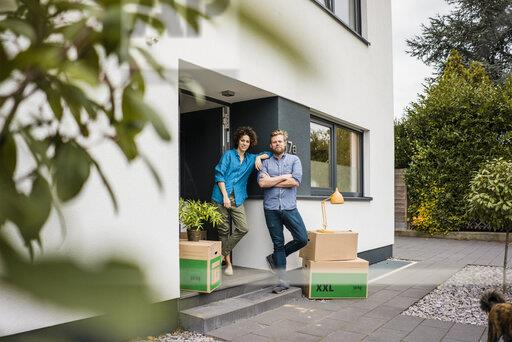 Couple standing at house entrance with cardboard boxes