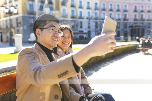 Spain, Madrid, young couple resting on a bench and taking a selfie in the city