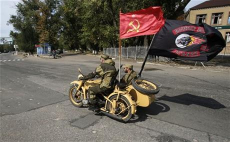 A Pro-Russian rebels bike arranged with a communist flag, left and Russian motorcycle club