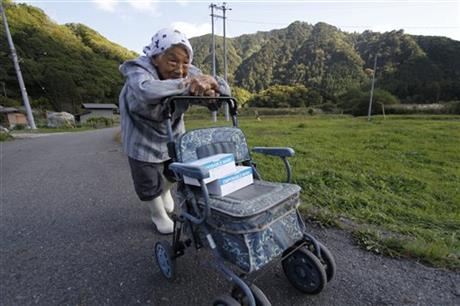 Yaeko Arai, 85, carries boxes of Surgical masks on her trolley as Mount Ontake continues to erupt in Otaki in Nagano Prefecture, central Japan, Wednesday, Oct. 1, 2014. Arai spent the afternoon handing a box of masks to each household as the village distributed more than 400 boxes of masks to 9 districts as a precaution for ash that may fall if eruptions worsen. The Japan Meteorological Agency said levels of toxic gases were too low to cause health problems in distant towns, but cautioned residents that ash could cause eye irritation, particularly among contact lens users, or trigger asthmatic symptoms. (AP Photo/Koji Ueda) (AP Photo/Koji Ueda)