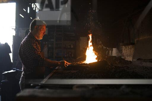 Blacksmith working at forge in his workshop