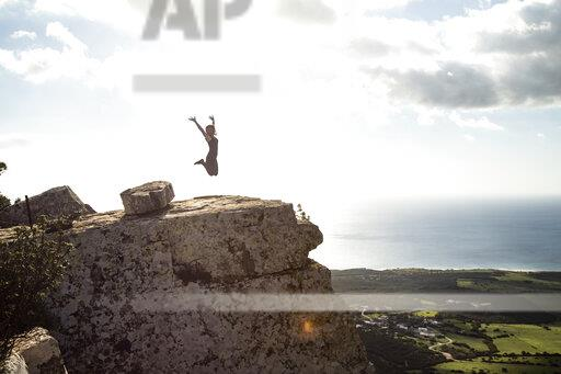 Young woman jumping on rock, raised arms