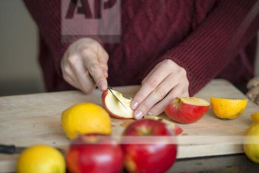 Hands of young woman cutting fruits on wooden board, close-up