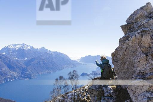 Italy, Como, Lecco, woman on a hiking trip in the mountains above Lake Como sitting on a rock enjoying the view
