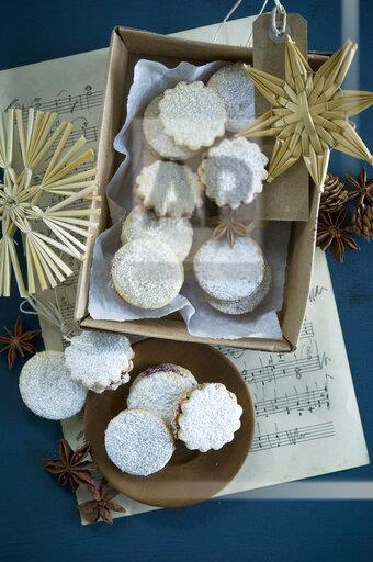 Christmas Cookies Spitzbuben in a box, music sheet, straw stars, star anise, larch cones, gift tag