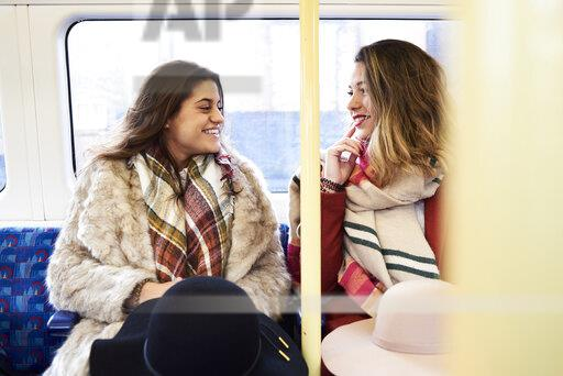 UK, London, two happy women in underground train