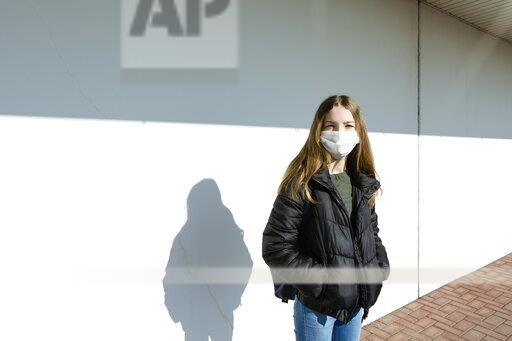 Girl with mask standing in front of a white wall
