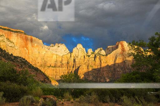 USA, Utah, Zion National Park, Early morning sunlight shining on the towering cliffs