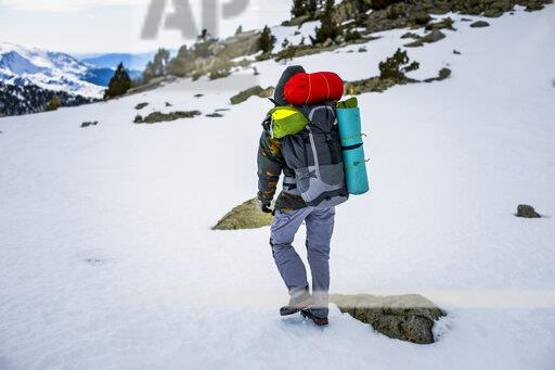 Rear view of man with backpack, snowcapped mountains