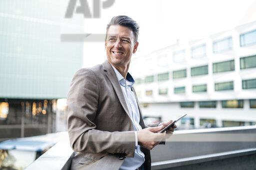 Smiling businessman with tablet on balcony in the city