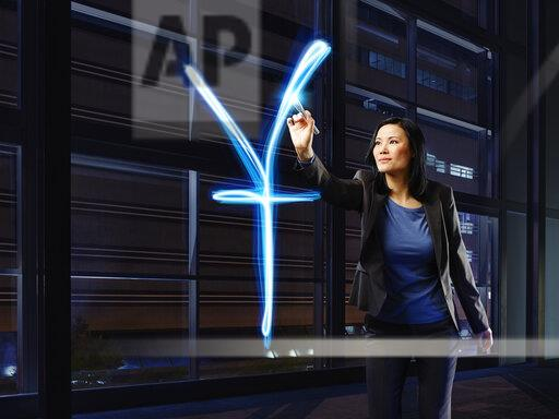 Asian businesswoman painting Yuan sign with light