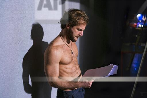 Shirtless actor looking at script at rehearsal