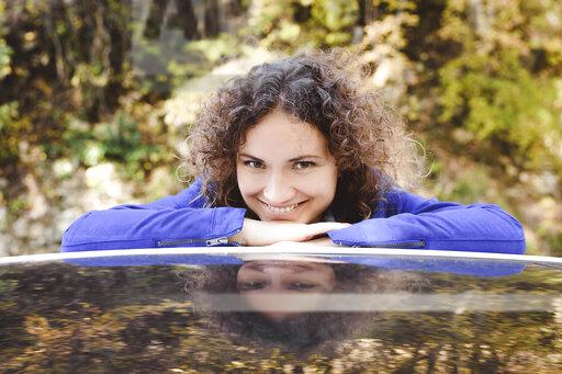 Portrait of smiling woman with curly hair leaning on car roof