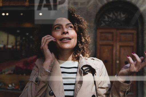 Portrait of woman talking on cell phone looking up