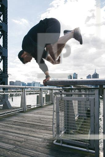 USA, New York, Brooklyn, young man doing Parkour handstand on railing of pier in front of Manhattan skyline