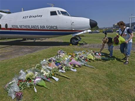 People lay flowers in front of a plane prior a ceremony to mark the return of the first bodies, of passengers and crew killed in the downing of Malaysia Airlines Flight 17, from Ukraine at Eindhoven military air base, Wednesday, July 23, 2014. After being removed from the planes, the bodies are to be taken in a convoy of hearses to a military barracks in the central city of Hilversum, where forensic experts will begin the painstaking task of identifying the bodies and returning them to their loved ones. (AP Photo/Martin Meissner)