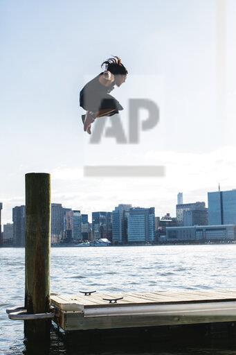 USA, New York, Brooklyn, young man doing Parkour jump from wooden pole in front of Manhattan skyline
